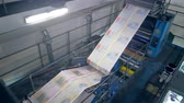 パブリッシング : Fresh printed newspaper moving through the printing press 動画素材