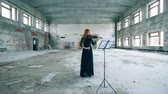 slierten : Female violinist plays a violin in an abandoned building.