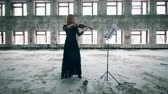 slierten : One woman plays a violin, standing in a ruined building. Stockvideo