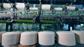 slierten : Sewing spools are mechanically unwinding at a textile factory.