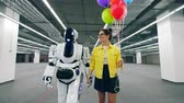 przyjaźń : Tall robot is walking with a young woman talking to it Wideo