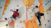 пять : A guy and a girl are high-fiving each other while climbing session Стоковые видеозаписи