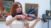 on : Female performer is playing the violin in a front view