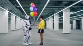 automat : One girl gifting balloons to a robot in a room. Dostupné videozáznamy