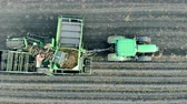 プラウ : Top view of an agricultural machine with workers driving through potato farmland
