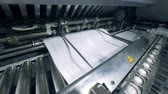 baskılar : Automated machine pushes paper onto a conveyor, typographic equipment.