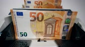 valores : Euro banknotes are getting counted by an automatic device