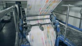 パブリッシング : Newspaper pages rolling on mechanical conveyor at a print office.