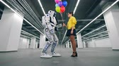 A girl gifting colorful balloons to her friend robot.