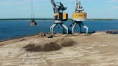 Dock crane carries a heap of breakstones in a metal bucket.