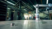 шестерня : Robotic arm moves gears on a table at a factory.