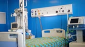 kussens : A bed and medical devices in a hospital ward.