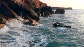 vibráló : Rocks are getting washed by the ocean. Travel, vacation, holidays concept. Stock mozgókép