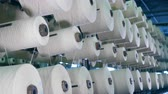 szövés : White threads are revolving with the spools. Industrial textile factory.