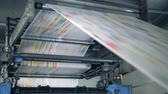 덮개 : Publishing house unit with paper rolling through the machine. Printing newspapers in typography.