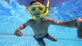 giymek : Little kid wears a mask while learning to swim in a pool. Underwater footage.