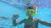giymek : Child wears a mask while swimming in a pool. Underwater footage.
