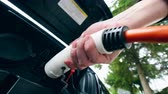 contactdoos : Man removes charging cable from a electric car socket. Charging of electric car.