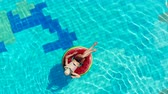 gonfiabili : Woman rests on a rubber ring in a pool.