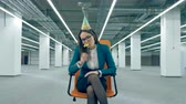 indifferent : Boring party concept. Sad female manager in a birthday hat is sitting in a rolling chair Stock Footage