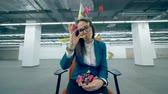 indifferent : Tired lady manager is sitting in a chair and throwing confetti. Boring party concept.