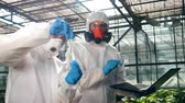 giymek : Two scientists in safety wear are analyzing a probe. Genetic modification concept. Stok Video