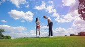 教師 : Man and woman training with clubs at a golf filed.