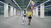 espaçoso : Human-like cyborg is walking with a girl holding balloons