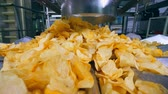 produtos químicos : Yellow chips falling from a tube onto a plant conveyor.