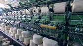 szövés : Mechanical sewing process of spools with white threads. Textile factory facility.
