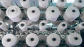 szövés : White threads are getting unwound from the rolling bobbins. Textile factory equipment. Stock mozgókép