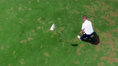 t şeklinde : A man puts a ball into a hole on a green course. Stok Video