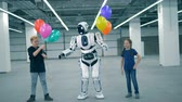 与える : Robot gives balloons to children, close up. School kid, education, science class concept.