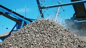 pedreira : Crushed stones falling from working belt. Mining industry concept.