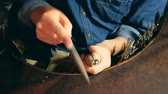 atölye : Male silversmith is burning the frame of the silver ring. A ring is getting polished by the silversmith Stok Video