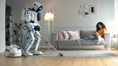 опрятный : A robot does vacuum cleaning while a girl lying on a couch. Cyborg and human concept. Стоковые видеозаписи