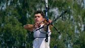 дартс : Front view of the male archer while aiming. Shooting with a bow and arrows in archery Стоковые видеозаписи