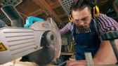 borotva : Male carpenter is using a rotary saw in his workshop Stock mozgókép