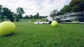 golfen : Yellow balls and metal clubs lying on a golf course.