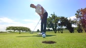 hráč golfu : Golfer tries to get a ball into a hole on a grass. Golf player on a golf course.