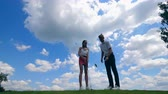 hráč golfu : Man teaches a woman how to play golf on a course.
