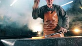 melting of metal : Forger hits hot knife with a hammer on anvil. Blacksmith forging iron in workshop. Stock Footage