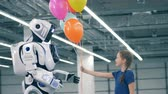 robô : A child gives balloons to a white robot, close up.