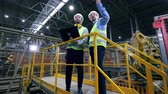 cantaria : Two engineers are having a discussion in the modern factory with robotic equipment