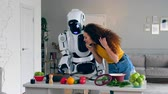 인간형 : A girl talks on the phone while a cyborg cooks food. Futuristic concept.
