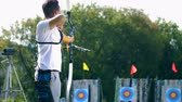 стрельба из лука : One man aims at a target, shooting a bow.
