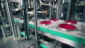 distribution automatique : Industrial conveyor is covering containers with foil Vidéos Libres De Droits