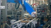 distribution automatique : Carton packages are being formed by a robotic mechanism
