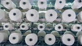 szövés : White threads coiling onto big bobbins at a textile plant.