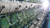 szövés : Metal machines work with threads at a textile factory, coiling them onto bobbins. Stock mozgókép